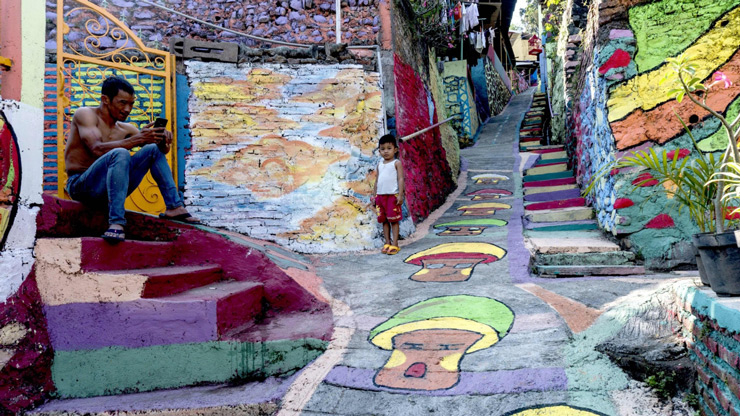 "gers relax along a path at an Indonesian hamlet dubbed ""the rainbow village"" in Semarang, central Java, that has become an internet sensation and attracting hordes of visitors."