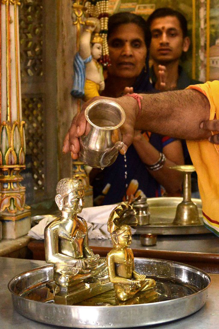 Jain priest is watched by devotees as he offers water to idols of Lord Mahavir, on the occasion of Mahavir Jayanti at a temple in Amritsar. The most important religious holiday in Jainism, Mahavir Jayanti celebrates the birth of Mahavira, the last Tirthankara, which is generally accepted as 599 BCE.