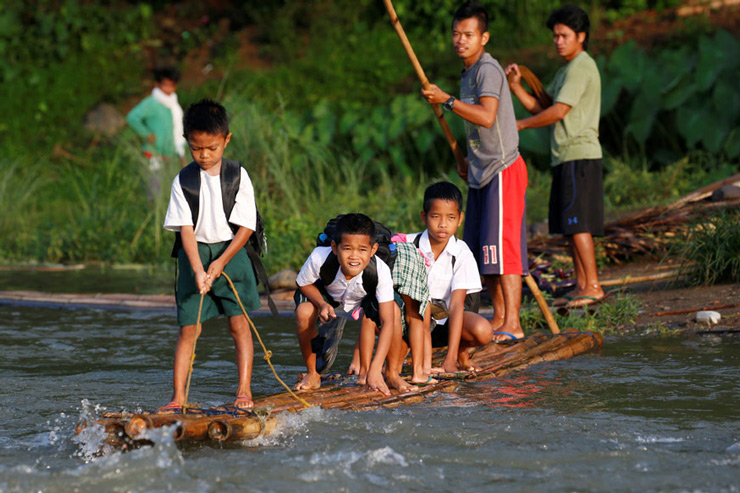 Schoolchildren ride on a makeshift raft to attend the opening of classes at a remote Casili Elementary School in Montalban, Philippines.