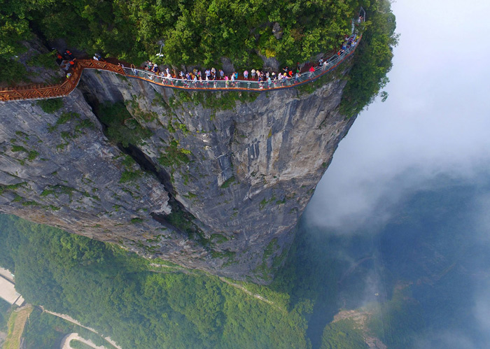 1.People walk along a high cliff wall on a glass-floored sightseeing walkway in Zhangjiajie, Hunan Province, China, on August 1, 2016.