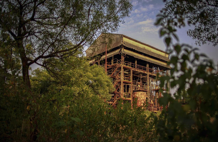1.Trees frame a rusting building at the abandoned former Union Carbide pesticide plant in Bhopal, India, on November 11, 2014. On the night of December 2, 1984, the factory owned by the U.S. multinational Union Carbide Corporation accidentally leaked methyl isocyanate and other highly toxic gases into the air, killing thousands of largely poor Indians in the neighborhoods nearby. #