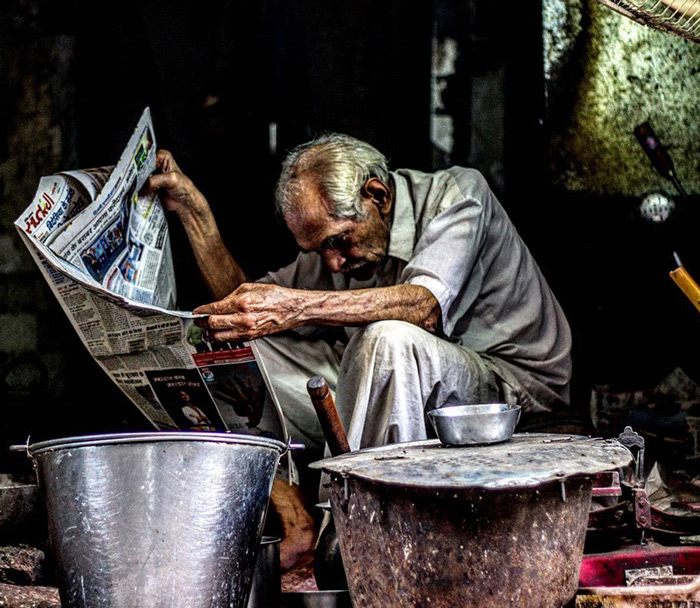 A shopkeeper is captured reading newspaper in free time.