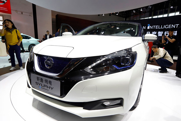 Visitors examine the newly unveiled Sylphy Zero Emission during the start of the Auto China 2018 in Beijing, China.