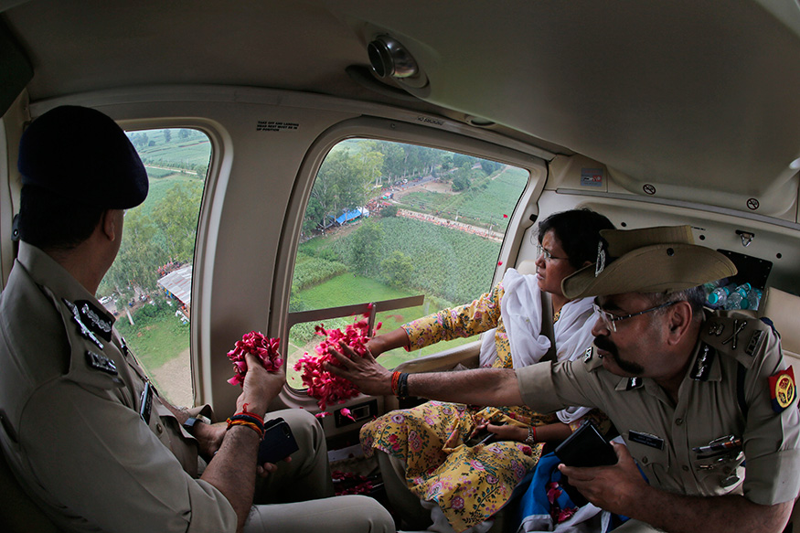 Government and police officials shower rose petals on Kanwarias from the helicopter near Meerut.