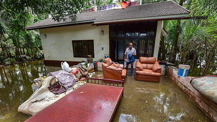 A man cleans up his house after flood water subsided, in Puthenvelikkara near Kochi.