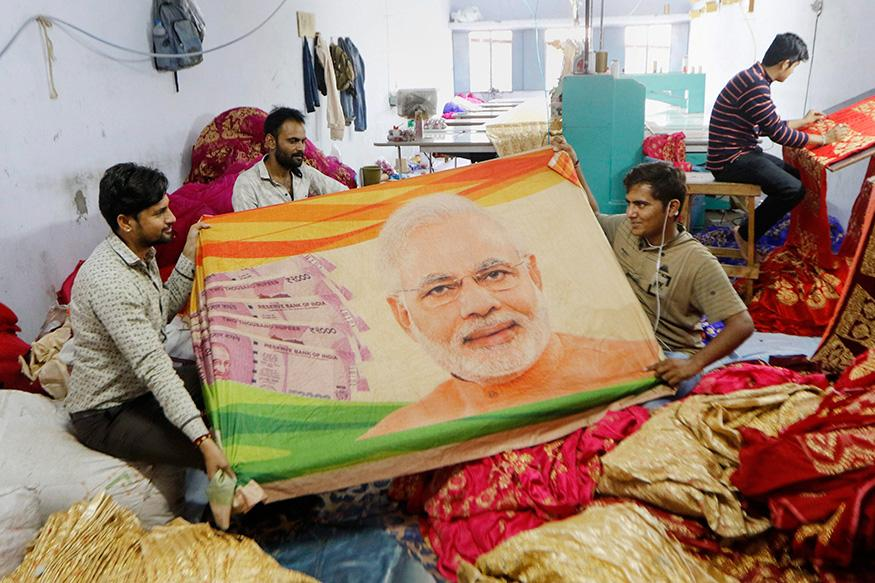 Salesmen display sarees with images of Prime Minister Narendra Modi printed on them, ahead of the Lok Sabha polls, at a shop in Surat.