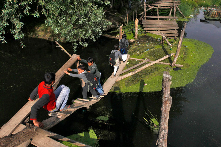 Kashmiri children cross a damaged footbridge built over a stream, on their way back home from school in Srinagar.