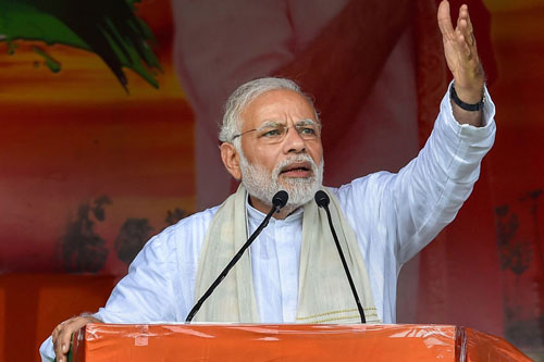 Prime Minister Narendra Modi reacts after a makeshift tent collapsed during his speech at a rally, in Midnapore district of West Bengal.
