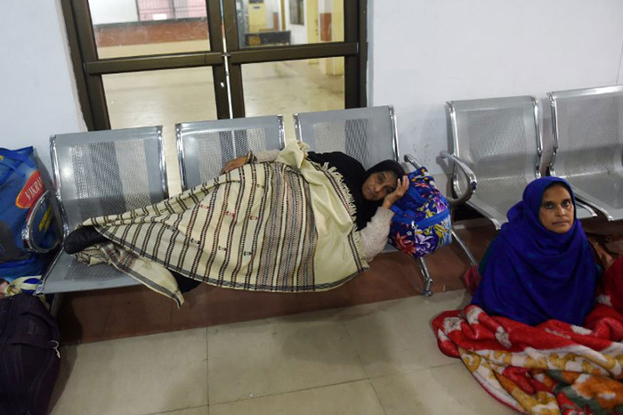 Stranded Indian passengers travelling with the Samjhauta Express sit and lay at the waiting area at Lahore railway station.
