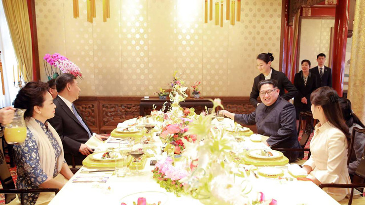 In this March 26, 2018, photo provided March 28, 2018 by the North Korean government, North Korean leader Kim Jong Un, center, smiles as he and Chinese counterpart Xi Jingping, center left, attend a banquet at the Great Hall of the People, in Beijing.