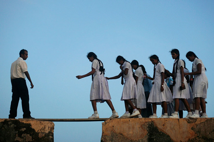 Schoolgirls walk across a plank on the walls of the 16th century Galle Fort in Sri Lanka.