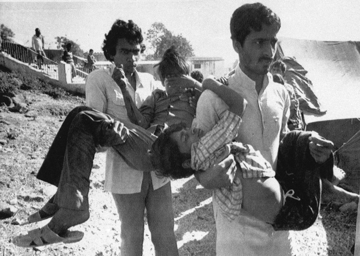 3.Two men carry children blinded by the Union Carbide chemical gas leak to a hospital in Bhopal on December 5, 1984. #