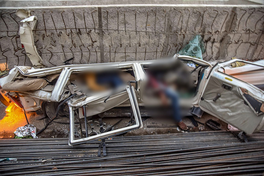 A crushed car after a portion of an under-construction flyover collapsed, leaving at least 18 dead.