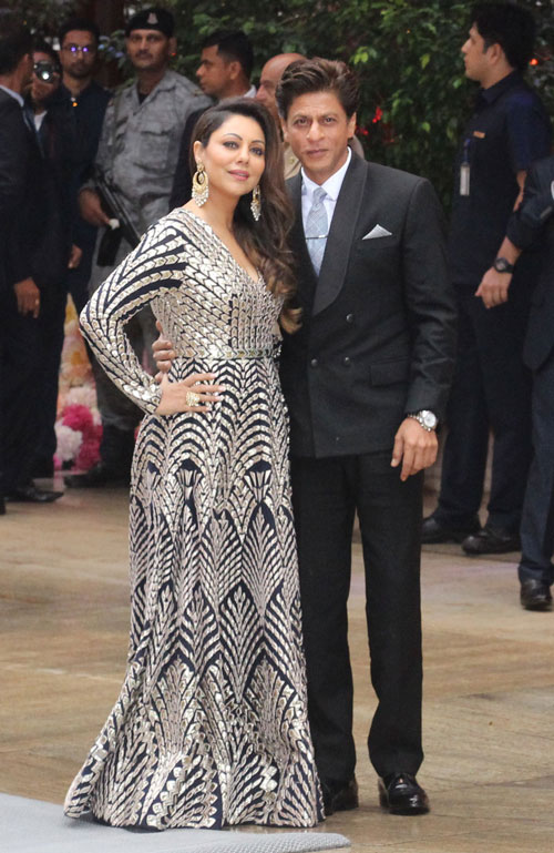 Shah Rukh Khan and Gauri Khan pose for photographers as they arrive for Akash Ambani and Shloka Mehta