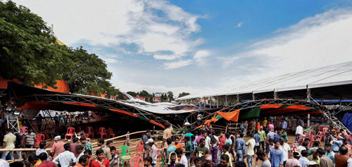 People stand near a tent that collapsed during Prime Minister Narendra Modi