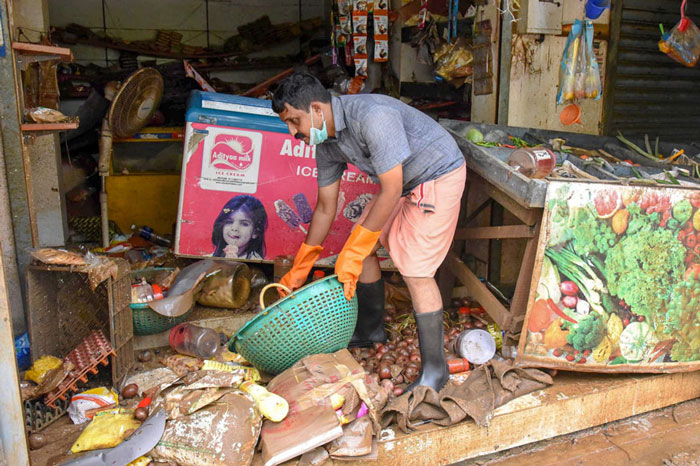 A man salvages the items at his shop after flood water receded at North Paravoor in Kochi.