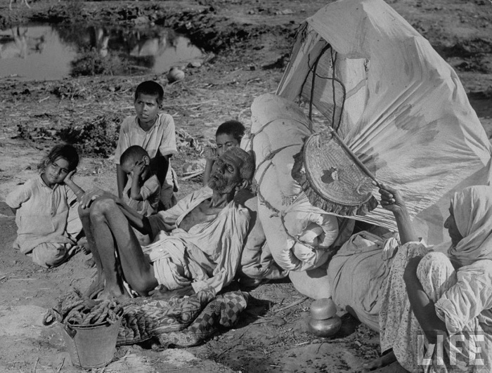A Muslim couple, along with their grandchildren, lies on the roadside after being exhausted by the travel. Hundreds walked past them, but none of the refugees attended to the plight of this family.