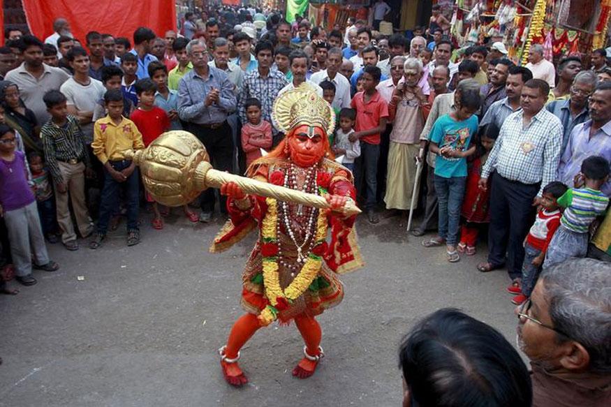 A man dressed as Hindu monkey god Hanuman performs on a street during Hanuman Jayanti Festival in Allahabad.