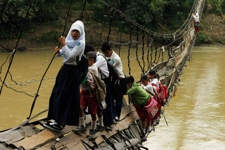 Students hold on to the side steel bars of a collapsed bridge as they cross a river to get to school in Indonesia