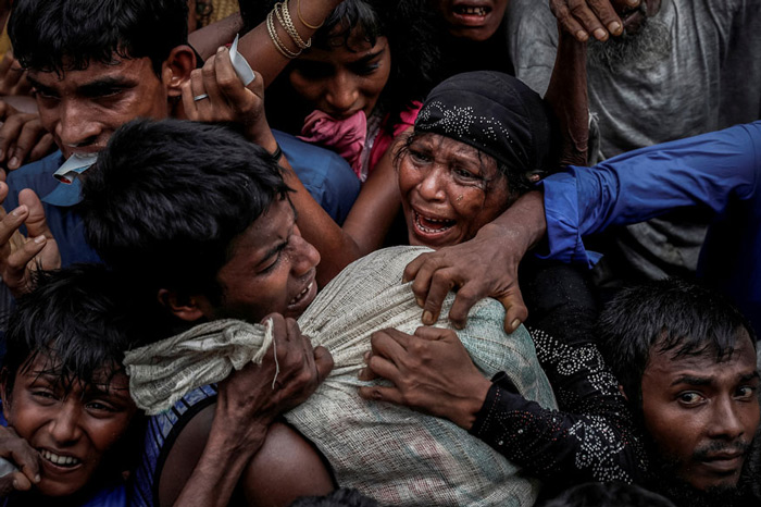Rohingya refugees scramble for aid at a camp in Cox