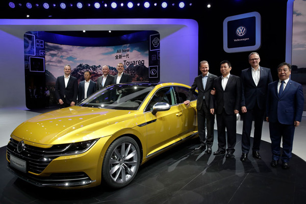 Herbert Diess, CEO of Volkswagen poses with officials and the next generation Volkswagen CC car model during the media day of the China Auto Show in Beijing.