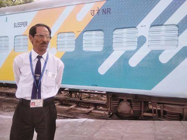 An official is seen standing next to the newly painted railway coaches.