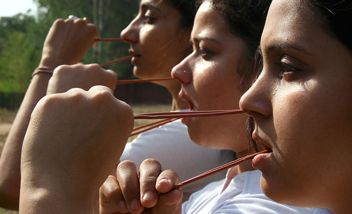 Students perform Rubber Neti, an ancient yogic technique, in Chandigarh. Many Indians believe that Rubber Neti controls the common cold, cough and asthma and keeps the nasal passages clean.
