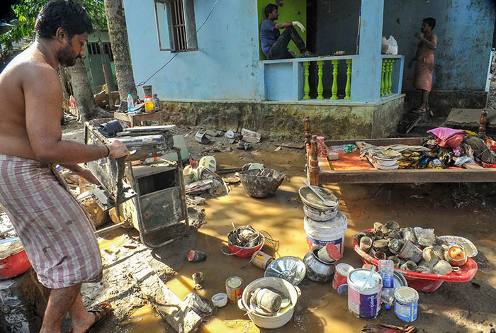 A man cleans up his house after flood water subsided at Chengannur district of the Kerala.