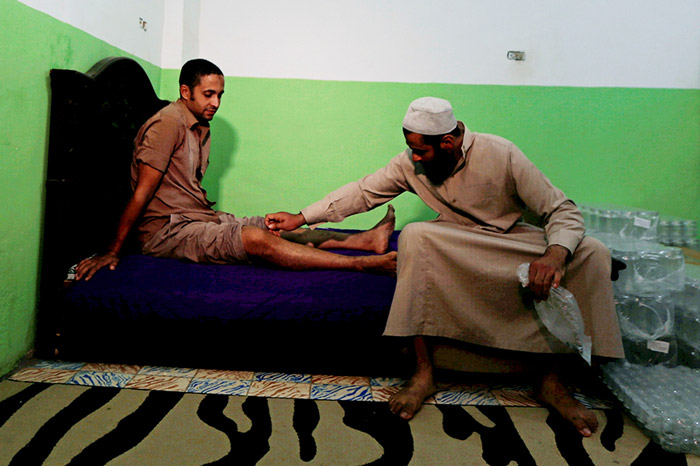 Health practitioner Haj Omar Abulhassan allows one of his bees to sting a patient suffering from leg problems in the treatment room of his home in Cairo, Egypt.