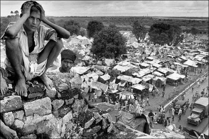 A young boy sits on what looks like a ruined wall of a fort