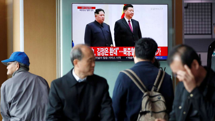 People watch a TV broadcasting a news report on a meeting between North Korean leader Kim Jong Un and Chinese President Xi Jinping in Beijing, in Seoul, South Korea - Reuters