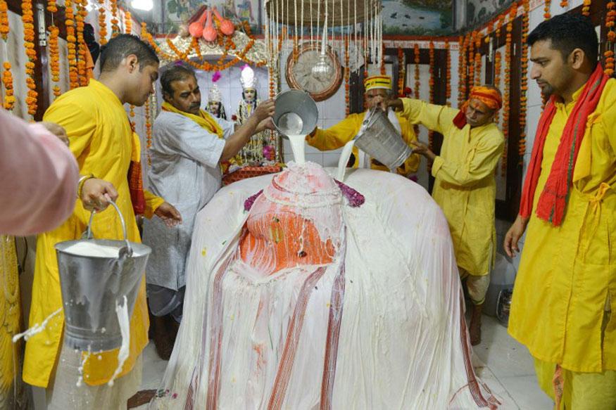 Hindu priests bathe a statue of the Hindu god Hanuman with milk at the Bara Hanuman Temple in Amritsar.