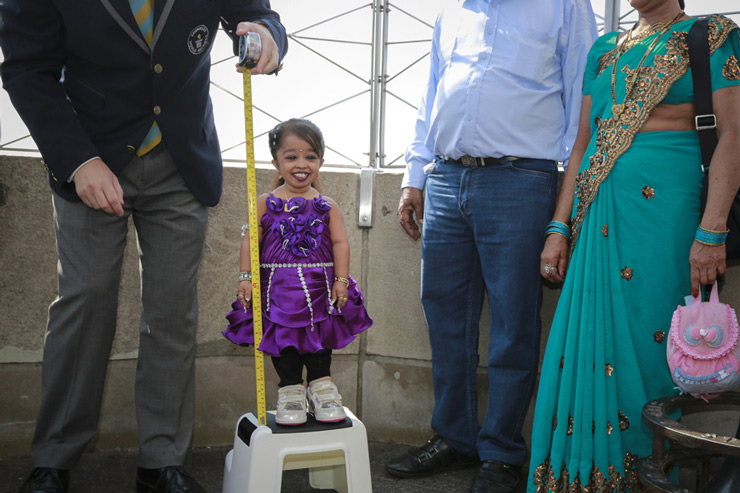 "Jyoti Amge,19, from Nagpur, India, is measured by a Guinness World Record official on top of the Empire State Building in New York. Standing 24.7 inches tall, Amge has held the title of the ""Shortest Living Woman"" since her 18th birthday on December 16, 2011."