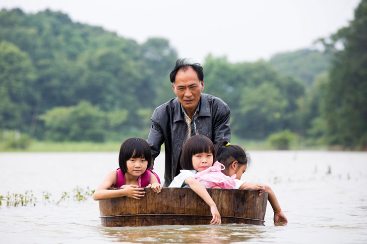 A man pushes a tub carrying children as he gets them back home after school in Duchang, Jiangxi Province, China.
