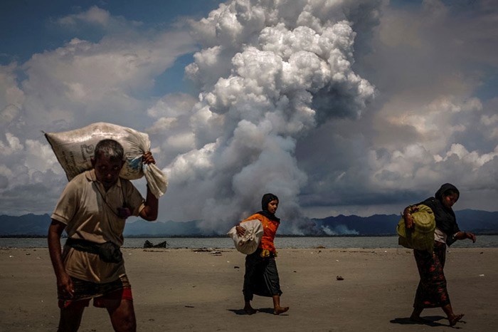 Smoke is seen on the Myanmar border as Rohingya refugees walk on the shore after crossing the Bangladesh-Myanmar border by boat through the Bay of Bengal, in Shah Porir Dwip, Bangladesh.
