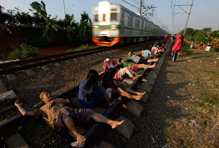 Residents lie on railway tracks in Rawa Buaya, Indonesia. The residents believe that the electrical energy from the tracks will cure them of various illnesses.