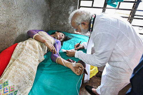 Prime Minister Narendra Modi visits a woman, who was injured after a portion of a tent collapsed at his rally, at a hospital in Midnapore.
