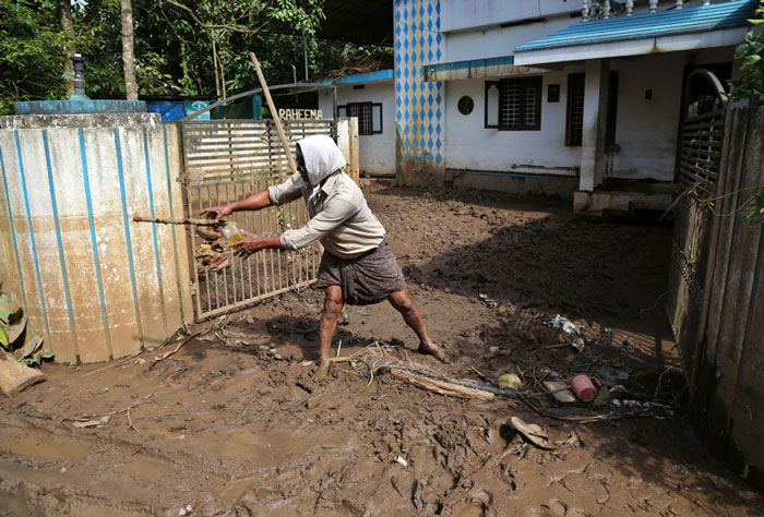 A man removes trash from sludge accumulated outside his flood affected house in Kochi.