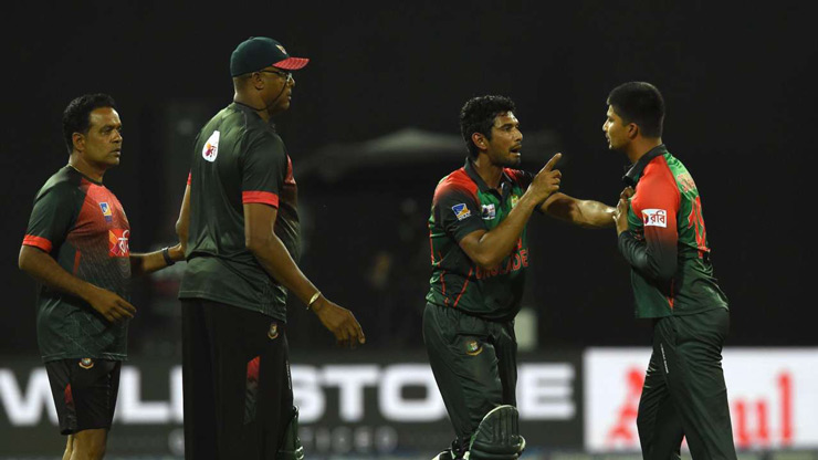 Bangladesh cricketer Nurul Hasan (R) exchanges words with Bangladesh cricketer Mahmudullah (2R) as coach Courtney Walsh (2L) looks on during the sixth Twenty20 (T20) international cricket match between Bangladesh and Sri Lanka of the tri-nation Nidahas Trophy at the R Premadasa stadium in Colombo on March 16, 2018.
