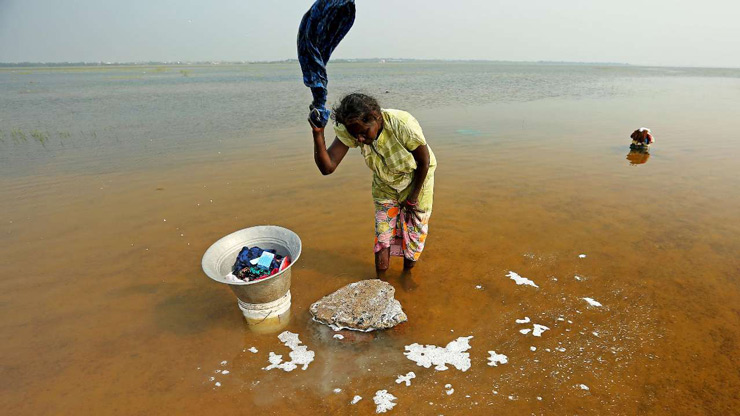 A woman washes clothes in the waters of Puzhal lake in Chennai.