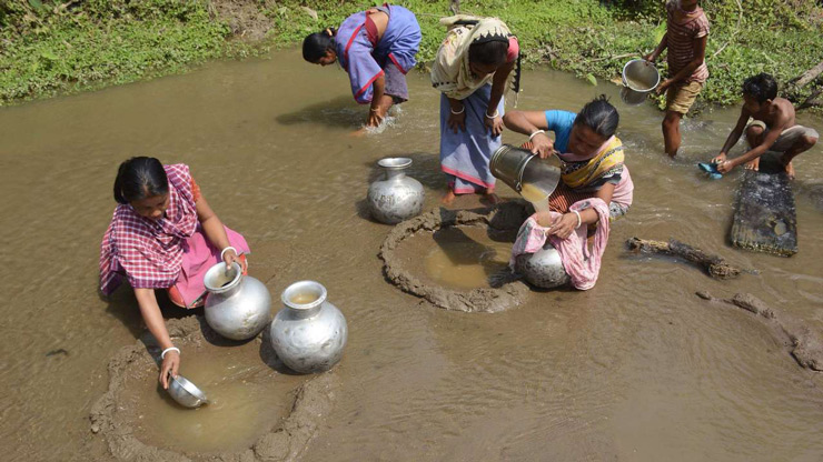 Women collect water from a small stream for drinking -- filtering out the mud and grit from the water with a cloth -- in Rupaichari village in Tripura