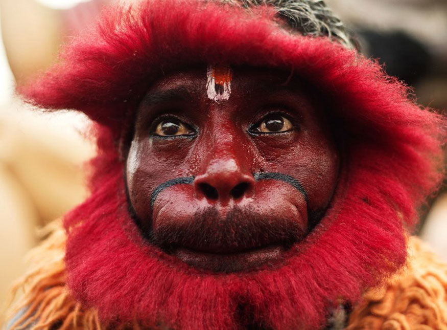 An Indian Hindu devotee dressed as a monkey takes part in a procession outside the Hanuman temple in New Delhi.