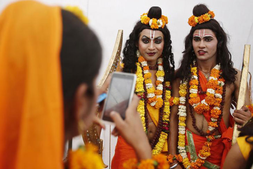A woman artiste uses a mobile phone to take pictures of her co-actors dressed as Hindu Lord Rama and his brother Laxman during a religious procession on the occasion of Hanuman Jayanti festival in New Delhi.