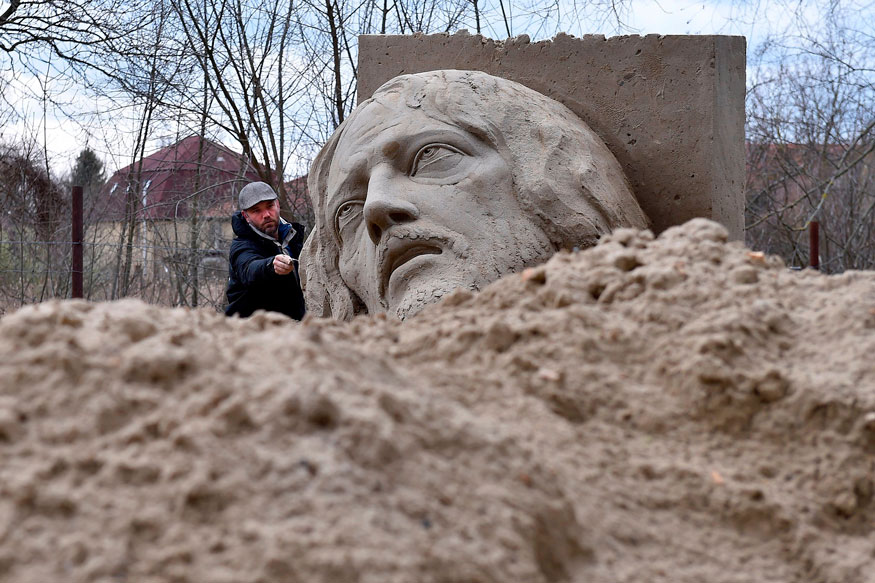Hungarian sculptor Ferenc Monostori puts the finishing touches to his sand sculpture depicting Jesus Christ in Tinnye, Hungary.