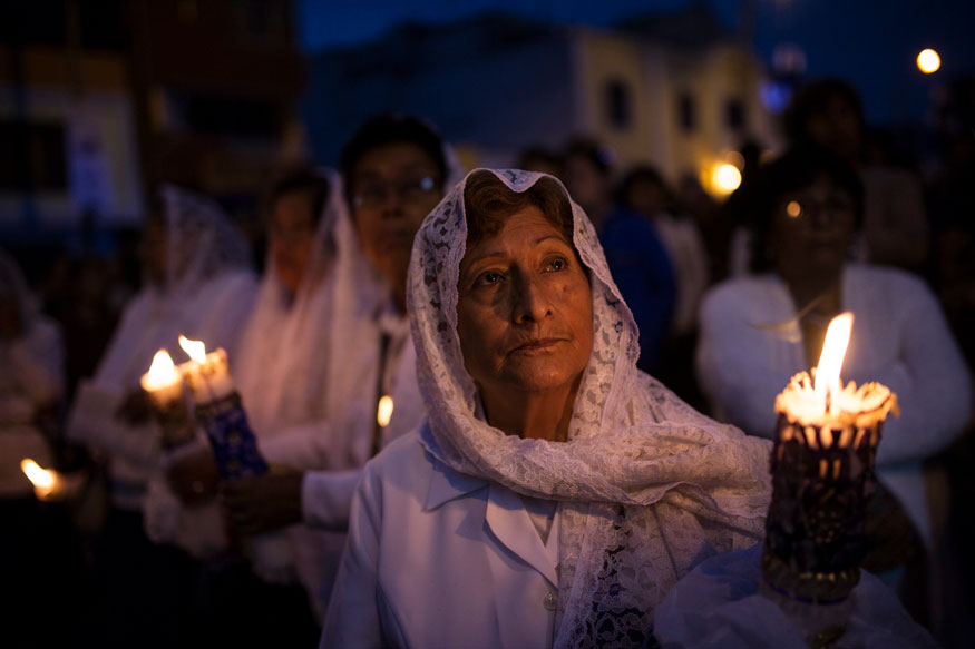 Faithful gather holding candles while taking part in a Holy Week procession in Lima, Peru.