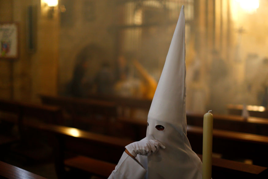 "A hooded penitent from the ""El Resucitado"" brotherhood takes part in a Holy Week procession in Cordoba, southern Spain."