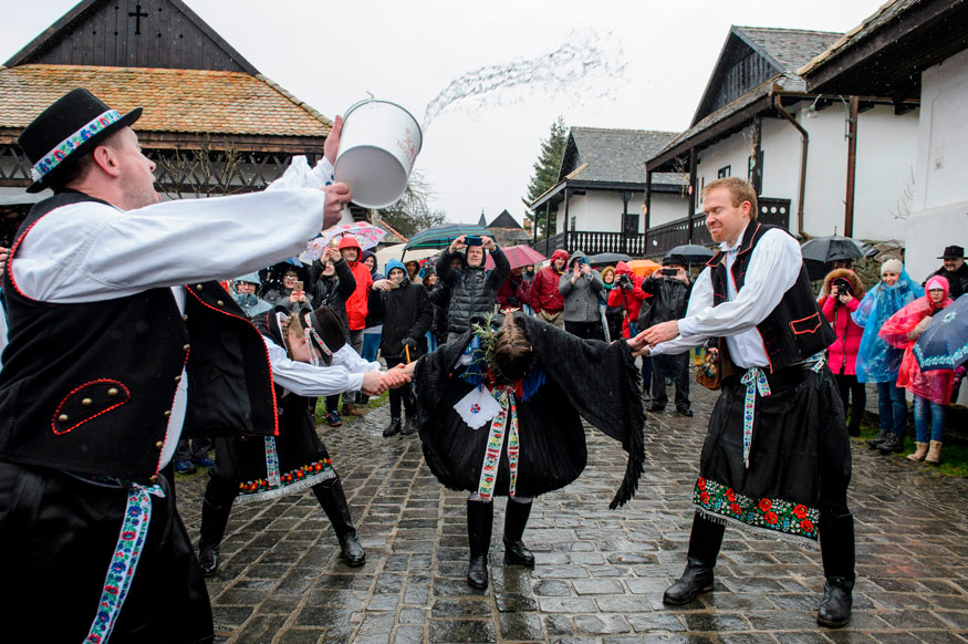 Dressed in folk costumes, young men pour water on young women in Holloko, a mountain village enlisted on the World Heritage List of Unesco in Hungary.