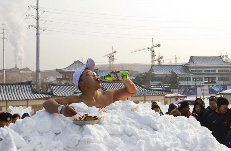 Jin Songhao drinks beer as he sits in snow during a cold endurance performance in Yanji, Jilin province. Jin set the Guinness record for the longest time spent in direct full body contact with snow with a time of 46 minutes and seven seconds, local media reported.