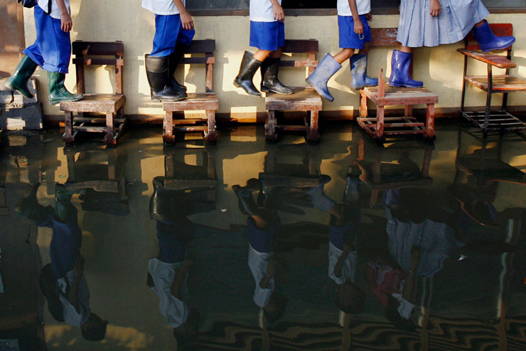 Students wearing rubber boots use chairs as a make-shift bridge to get to a classroom at Sitio Tapayan elementary school in Taytay, Manila.