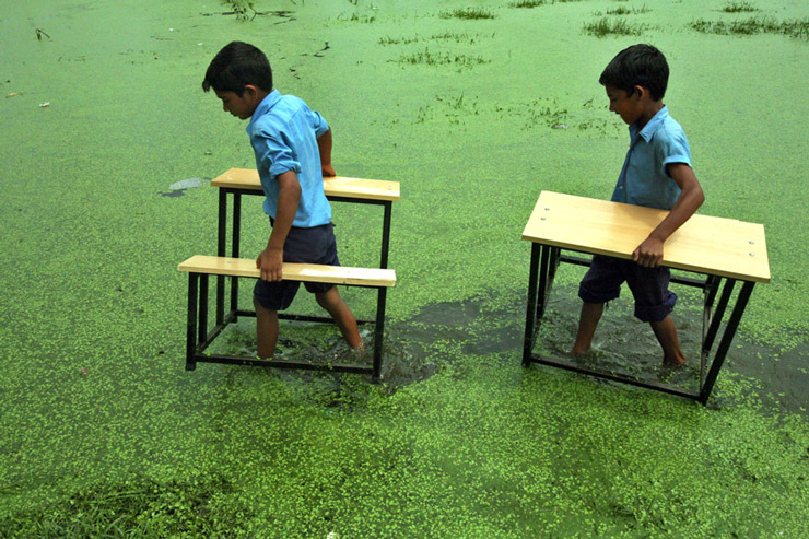 Primary school boys carry their benches to an open area after their school was flooded due to heavy rains in Jammu.